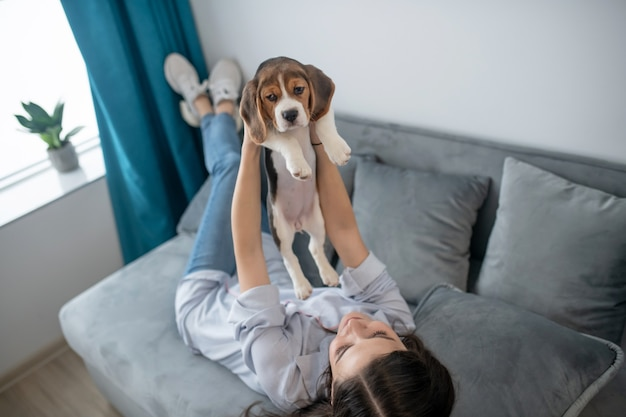 Menina de cabelos escuros com seu cachorrinho em casa se sentindo em paz