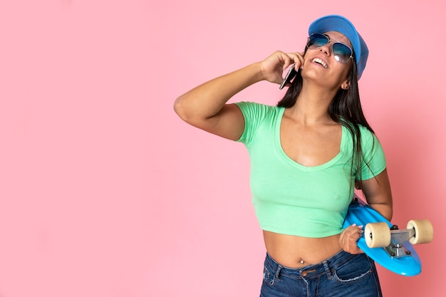 Menina de cabelos escuros, vestindo um boné na cabeça com o estilo de moda, segurando um skate e fala ao telefone
