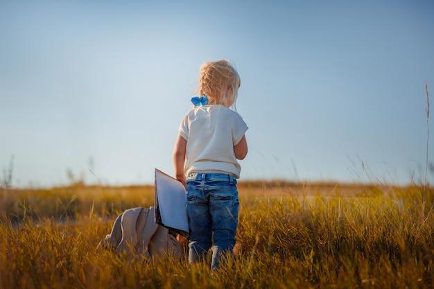 Menina de cabelos loiros com um livro sobre a natureza. desenvolvimento infantil.