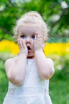 Menina de cabelos loiros em um vestido branco mantém as mãos nas bochechas e mostra surpresa