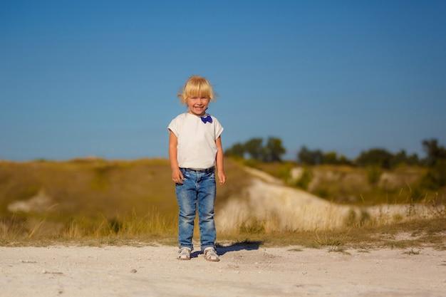 Menina de cabelos loiros joga jogos ao ar livre, em uma caminhada na natureza.