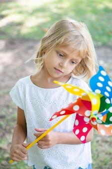 Menina de cabelos loiros pensativa em pé no parque, segurando o cata-vento, olhando para o brinquedo. tiro vertical. conceito de atividade infantil ao ar livre