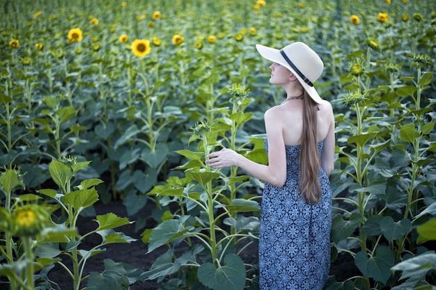 Menina de cabelos longos em um chapéu e vestido fica de costas contra o de um campo de girassol florescendo. vista traseira