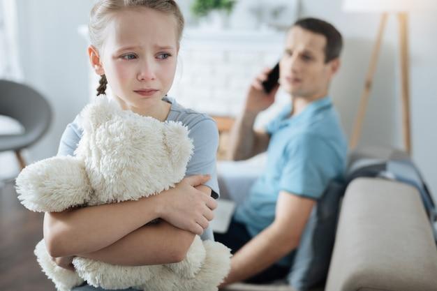 Menina de cabelos louros infeliz de olhos azuis segurando seu brinquedo e chorando enquanto seu pai fala ao telefone