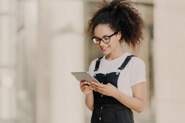 Menina de cabelos muito encaracolada olha para a tela do tablet digital com sorriso, lê algum texto ou livro eletrônico