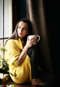 Menina de cabelos negros concebida está olhando pela janela e tomando chá