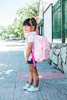 Menina de cabelos negros usando uma mochila rosa na rua
