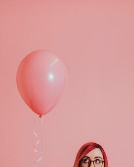 Menina de cabelos rosa com um balão