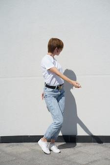Menina de cabelos ruivos dançando na luz do sol na frente de paredes brancas no verão