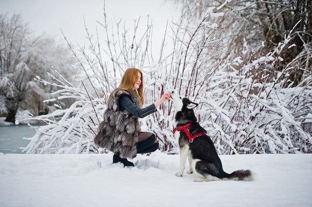 Menina de cabelos vermelha andando no parque com cães husky em dia de inverno.