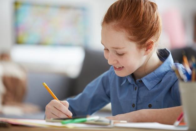 Menina de cabelos vermelha fazendo lição de casa