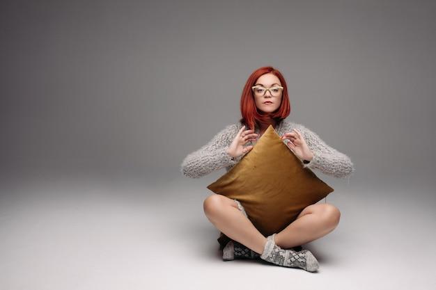 Menina de cabelos vermelha no suéter cinza e meias quentes, sentada no chão