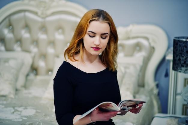 Menina de cabelos vermelha no vestido preto, sentado na cama e lendo a revista de moda