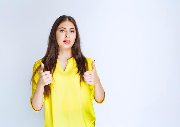 Menina de camisa amarela, mostrando o polegar para cima o sinal.