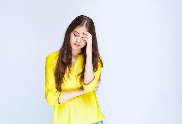 Menina de camisa amarela parece cansada ou tem dor de cabeça.