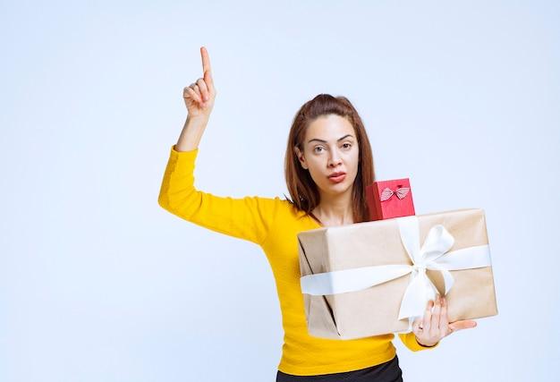 Menina de camisa amarela segurando caixas de presente e apontando para cima.