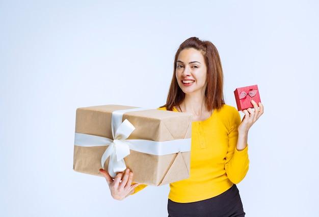 Menina de camisa amarela segurando caixas de presente.