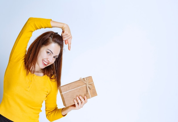 Menina de camisa amarela segurando uma caixa de presente de papelão.