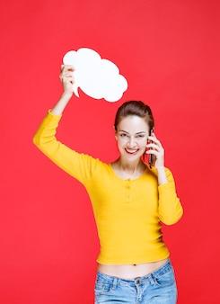 Menina de camisa amarela segurando uma placa de informações de forma de nuvem e falando ao telefone.