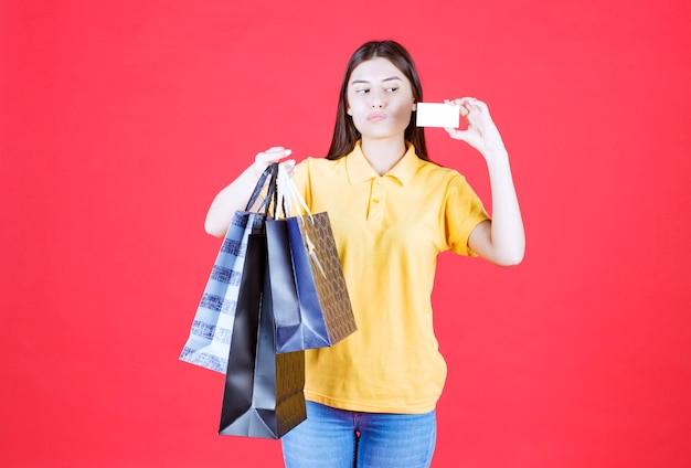 Menina de camisa amarela segurando várias sacolas de compras azuis e apresentando seu cartão de visita