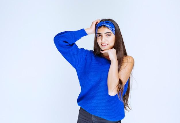 Menina de camisa azul dando poses sedutoras e alegres.