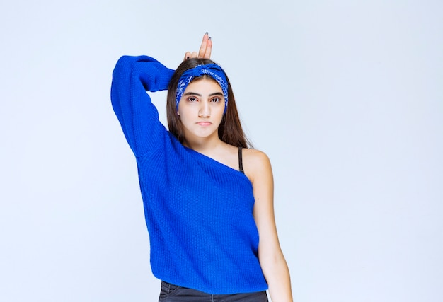 Menina de camisa azul, mostrando orelhas de coelho.