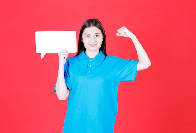 Menina de camisa azul segurando um quadro retangular de informações e mostrando um sinal positivo