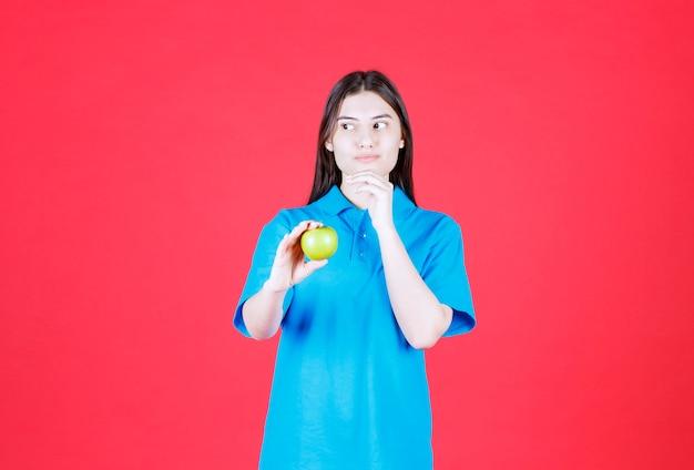 Menina de camisa azul segurando uma maçã verde e pensando e hesitando
