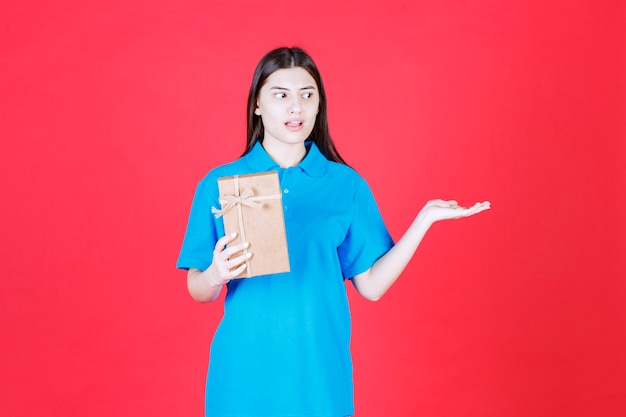 Menina de camisa azul segurando uma mini caixa de presente de papelão e chamando alguém para se aproximar e pegá-la