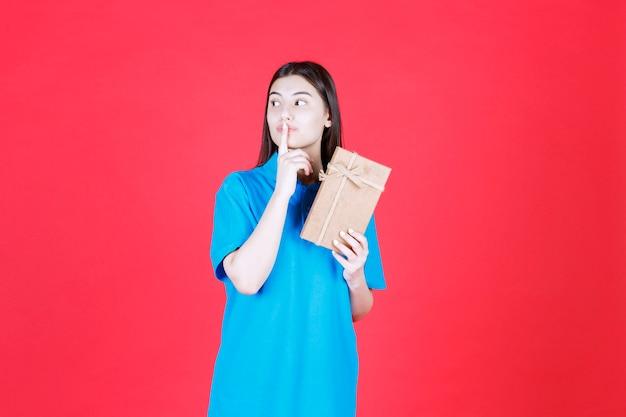 Menina de camisa azul segurando uma mini caixa de presente de papelão e parece confusa