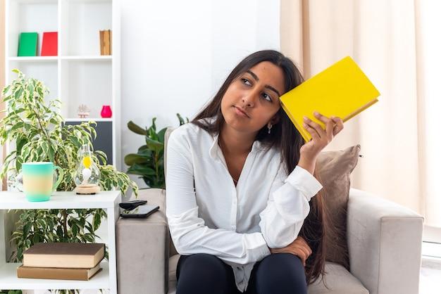 Menina de camisa branca e calça preta segurando um livro, olhando para o lado confusa, sentada na cadeira na sala iluminada