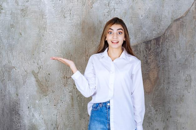 Menina de camisa branca em pé em uma parede de concreto e percebendo a pessoa ao redor.