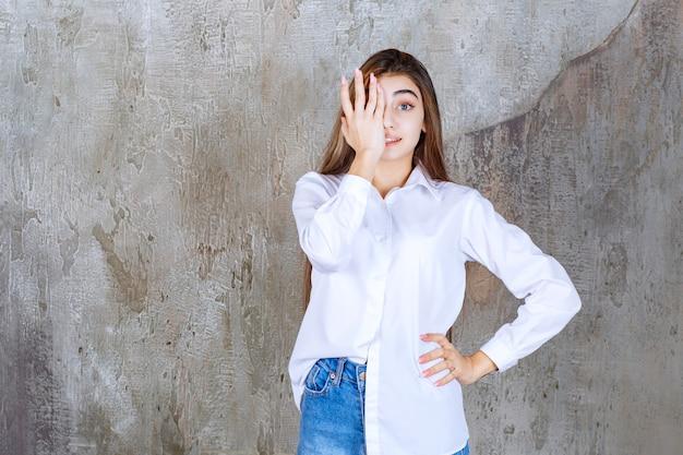 Menina de camisa branca em pé em uma parede de concreto e se sentindo assustada e apavorada.