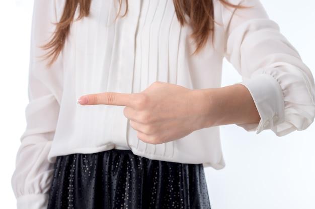 Menina de camisa branca puxou sua mão para o lado e mostra o dedo indicador em direção ao
