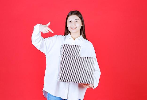 Menina de camisa branca segurando duas caixas de presente de prata e apontando para algum lugar