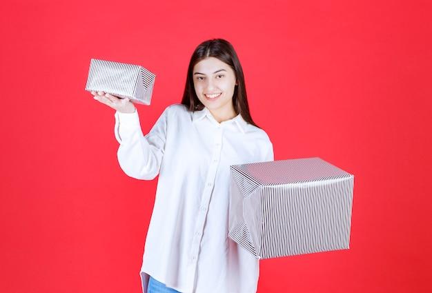 Menina de camisa branca segurando duas caixas de presente prateadas com as duas mãos e fazendo uma escolha