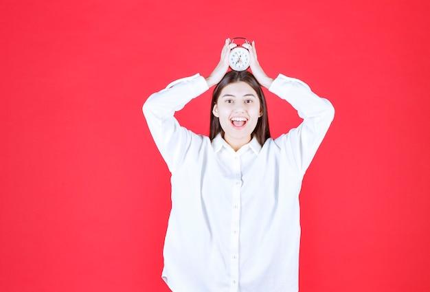 Menina de camisa branca segurando um despertador na cabeça e parece animada