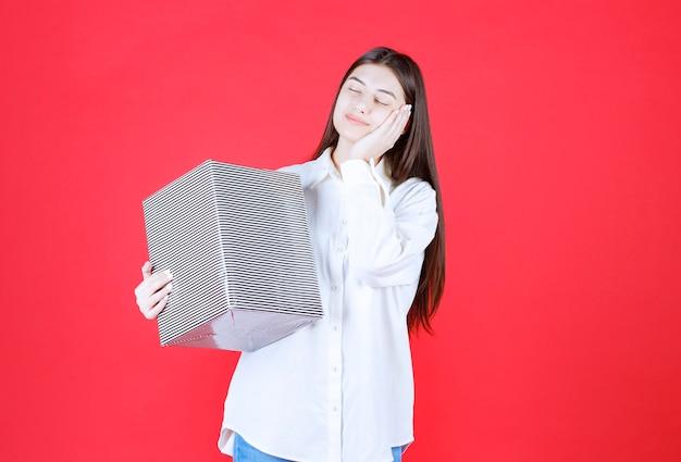 Menina de camisa branca segurando uma caixa de presente prata parecendo cansada e com sono