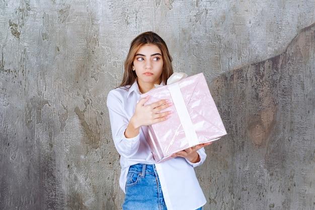Menina de camisa branca segurando uma caixa de presente rosa embrulhada com fita branca e parece assustada ou apavorada.