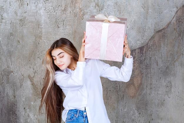 Menina de camisa branca segurando uma caixa de presente rosa embrulhada com fita branca e sacudindo-a.