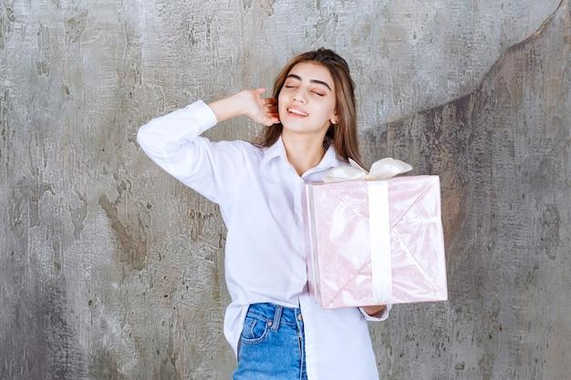 Menina de camisa branca segurando uma caixa de presente rosa embrulhada com fita branca e se sentindo cansada e com sono.
