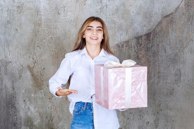Menina de camisa branca segurando uma caixa de presente rosa embrulhada com fita branca, notando seu parceiro e pedindo-lhe para vir recebê-la.