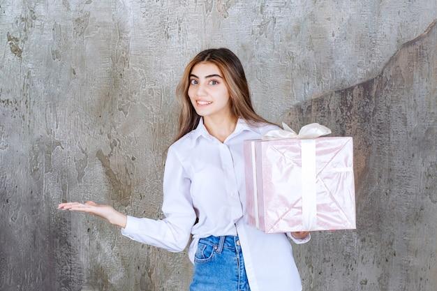 Menina de camisa branca segurando uma caixa de presente rosa embrulhada com fita branca, notando seu parceiro e pedindo-lhe para vir recebê-la