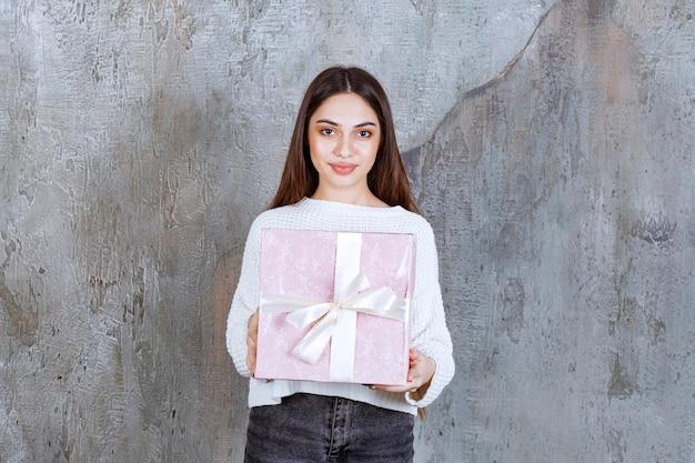 Menina de camisa branca segurando uma caixa de presente roxa.