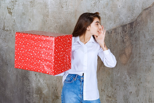 Menina de camisa branca segurando uma caixa de presente vermelha com pontos brancos e chamando alguém para lidar com isso.