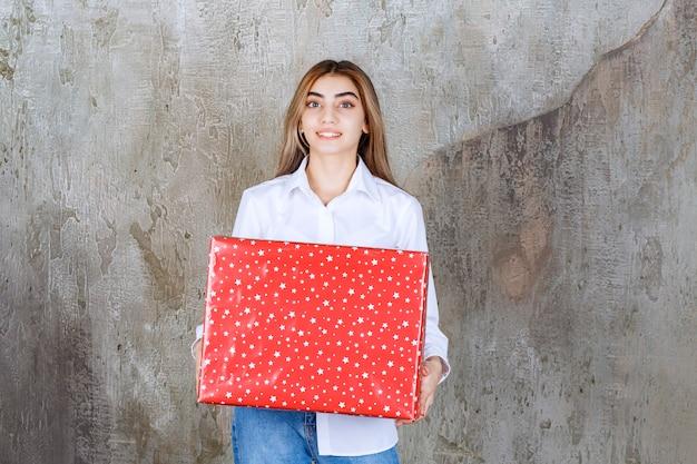 Menina de camisa branca segurando uma caixa de presente vermelha com pontos brancos.