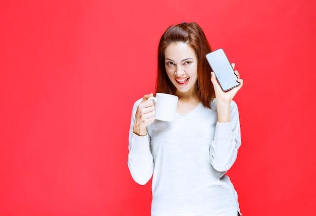 Menina de camisa branca segurando uma caneca de café branca e um smartphone preto.