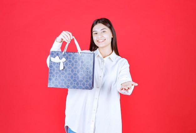 Menina de camisa branca segurando uma sacola de compras azul e convidando alguém para apresentá-la