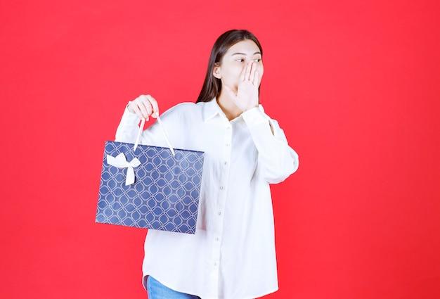 Menina de camisa branca segurando uma sacola de compras azul e ligando para alguém