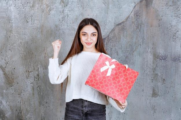 Menina de camisa branca segurando uma sacola de compras vermelha e mostrando sinal de mão positiva.